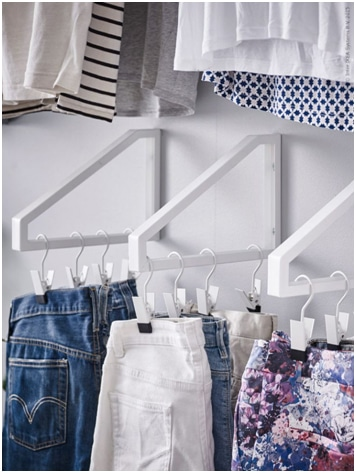 White hanger rack in small closet with pants