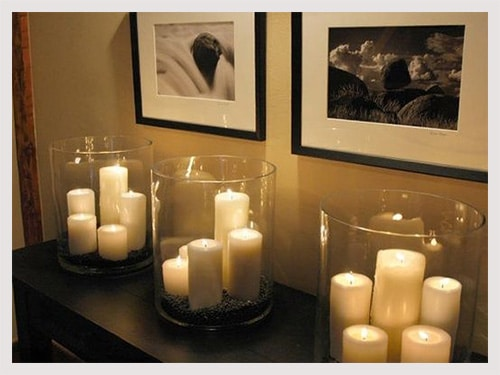 Romantic candles on shelf in bedroom with pictures