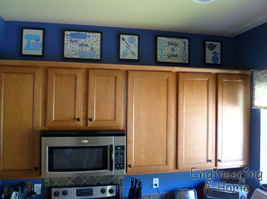 Art gallery above cabinets in blue kitchen