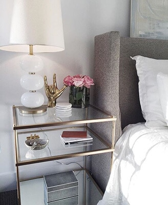 Glass side table next to bed