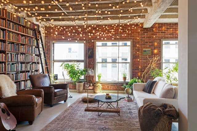 String Lights in room with brick wall and large bookshelves