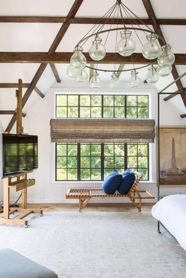small living room with easel tv stand in white bedroom with beams