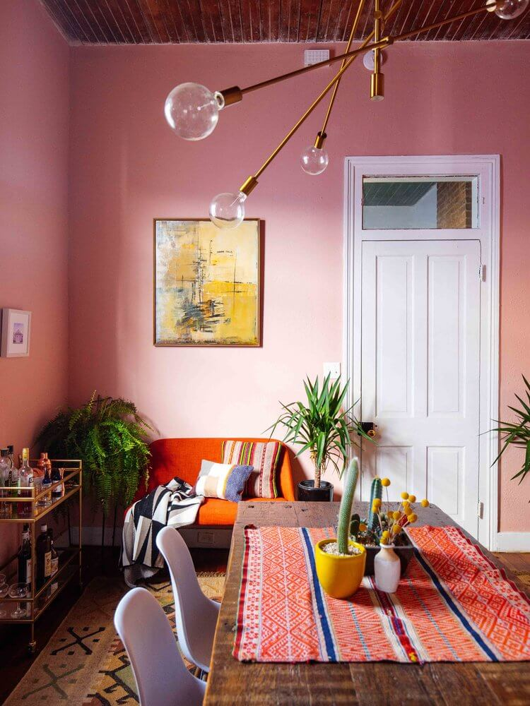 Pink dining room with artwork, plants and fancy lights