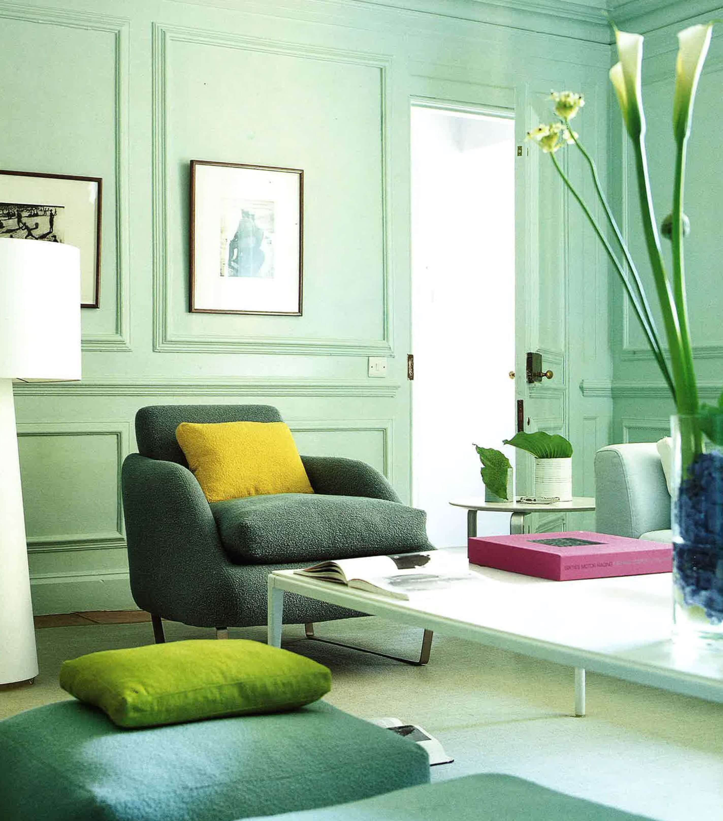 Light green living room with coffee table, plants and framed artwork