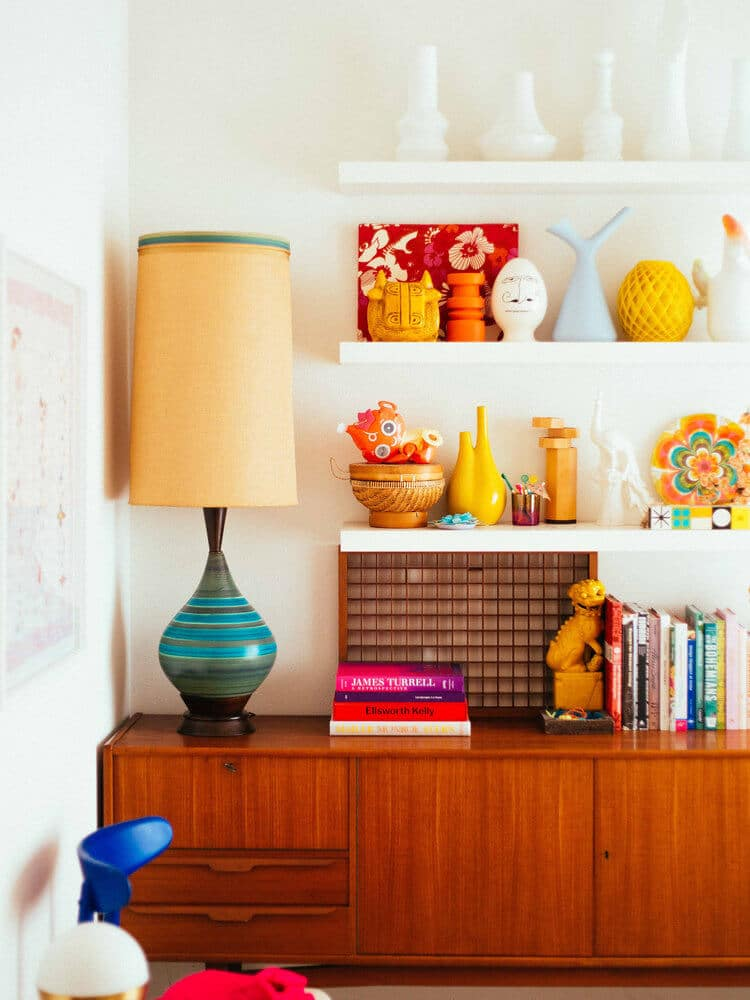 White shelves with colorful decor and wooden cabinet