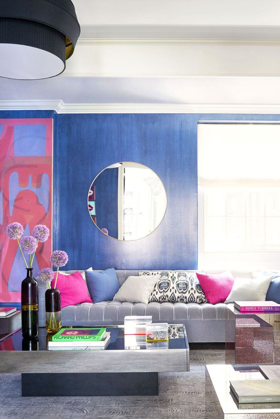 Royal blue living room with grey couch and coffee table plus other decor