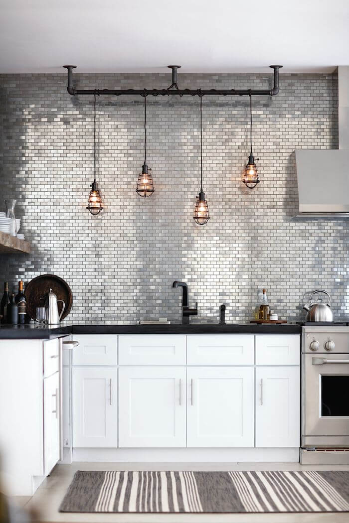 Metal kitchen backsplash in white kitchen with black accents and pendant lights