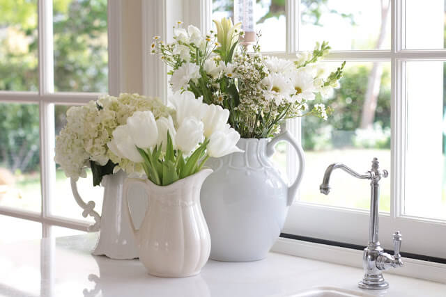 Plants and blooms in white vases on a white Kitchen Counter Corner