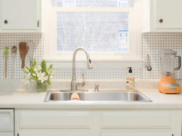 Pegboard backsplash in a white kitchen with windows and plants