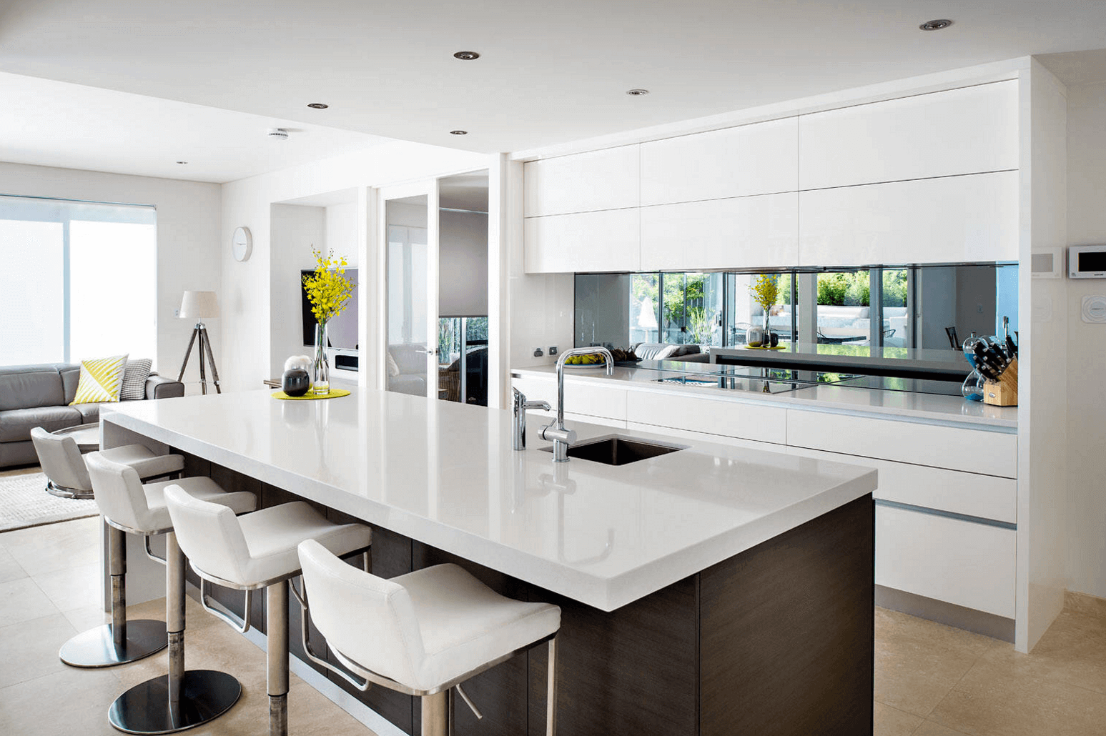 Mirror backsplash in white kitchen with white counter top island and plant