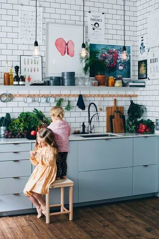 White kitchen with subway tile, artwork and pendant lighting, with plants