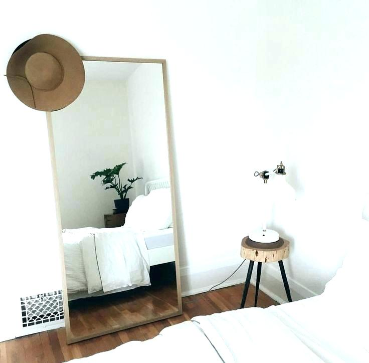 modern minimalist bedroom with white table lamp and floor mirror
