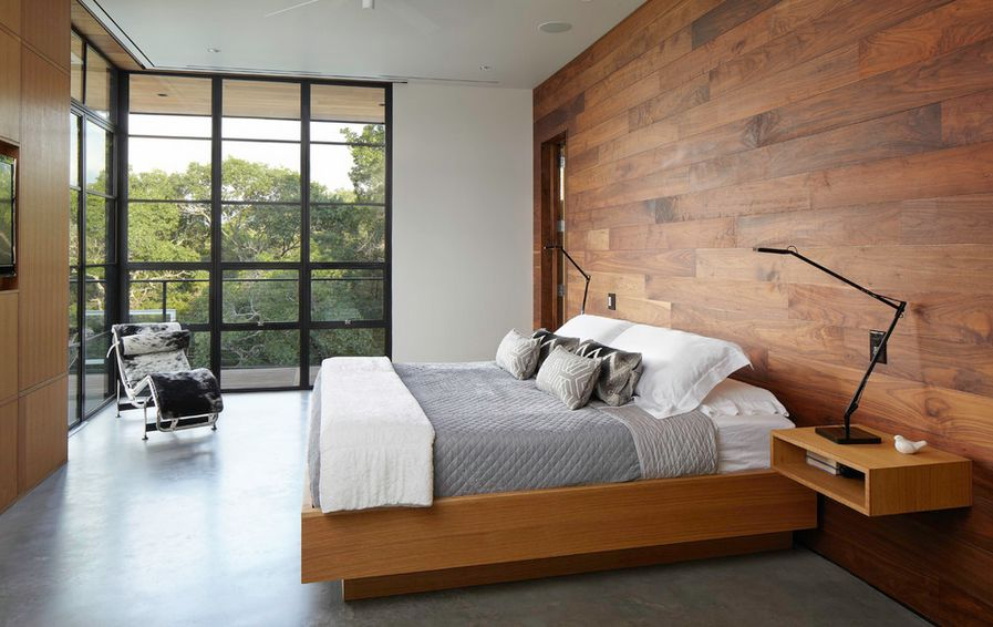 Minimalist bedroom with wood paneling walled windows and white chair