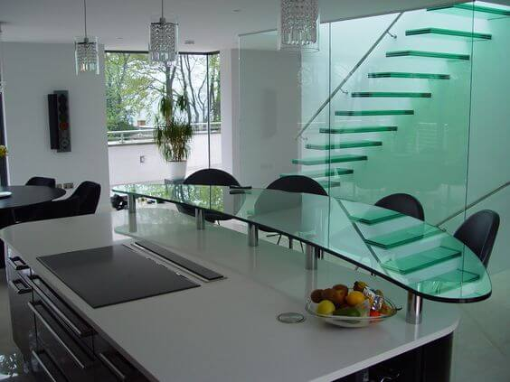 Floating glass bar on island in black and white kitchen