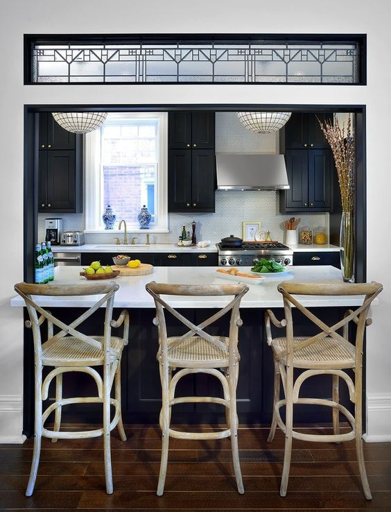 Kitchen wall cut out breakfast bar with white countertops and wicker bar chairs
