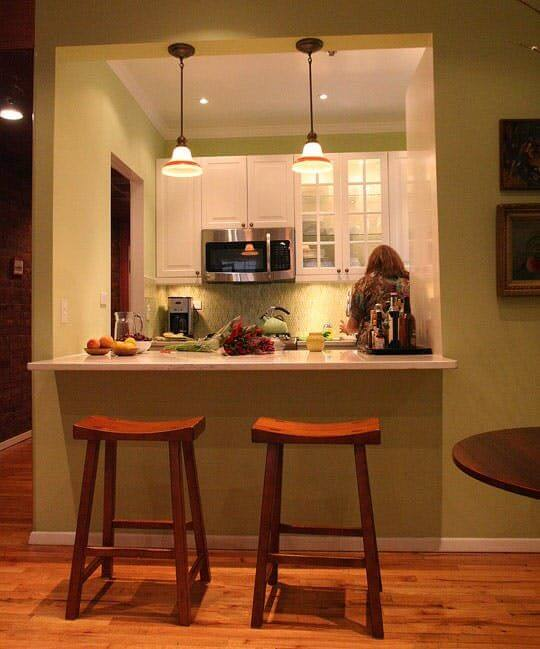 Wall cut out bar with wooden stools in pastel green kitchen