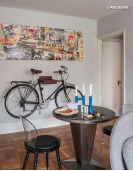 Bike on the wall with wall art and small table