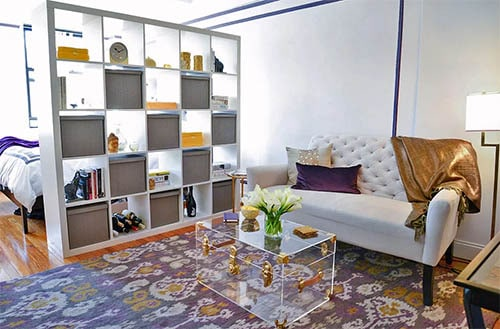 Book shelf room divider studio with white couch and decor