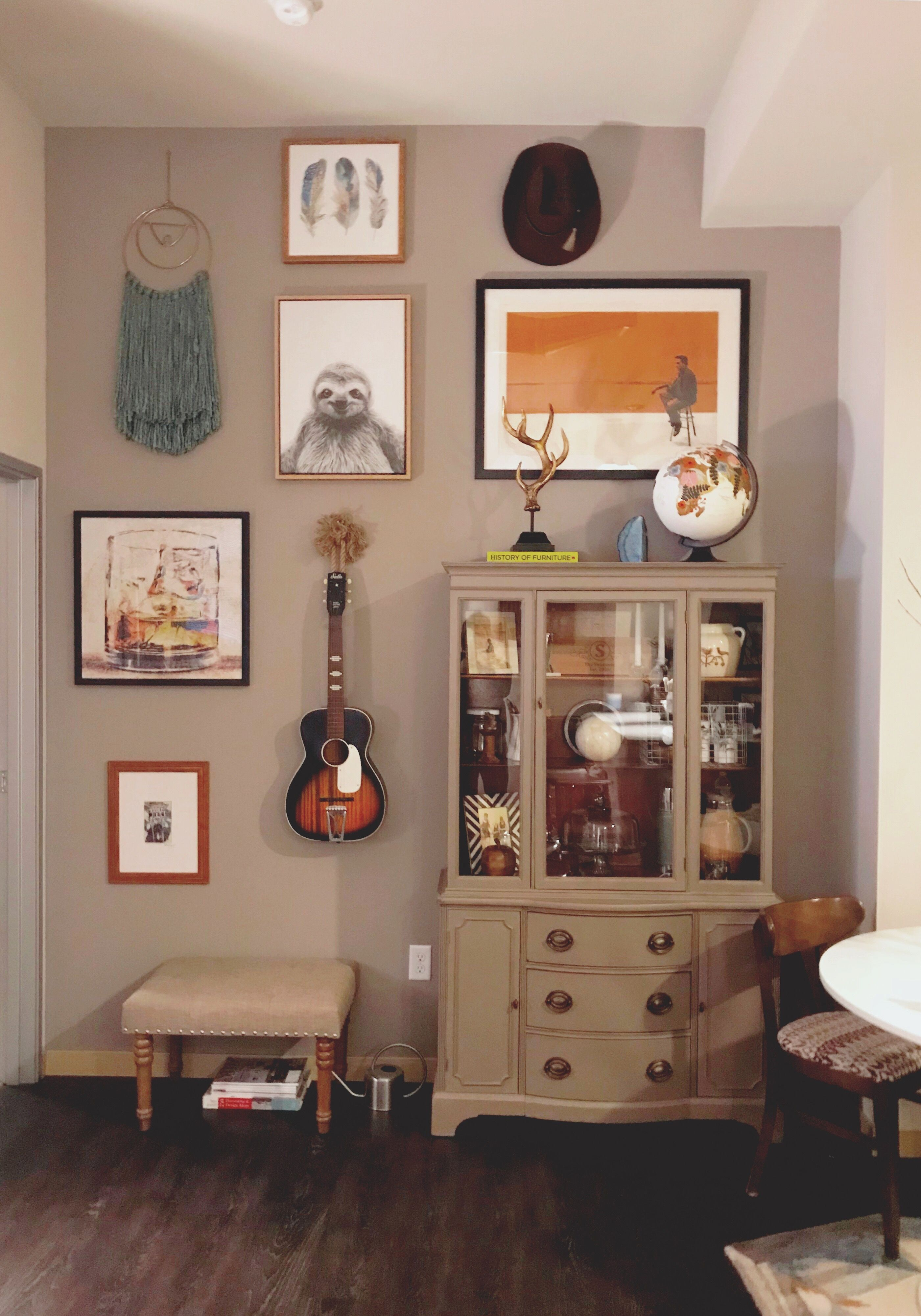 Guitar on wall with cabinet wall art and brown decor