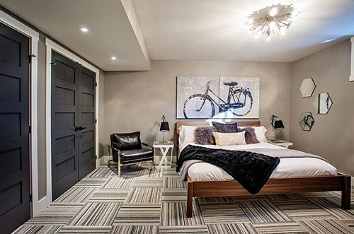 bachelor pad bedroom with geometric pattern design with black doors and other decor