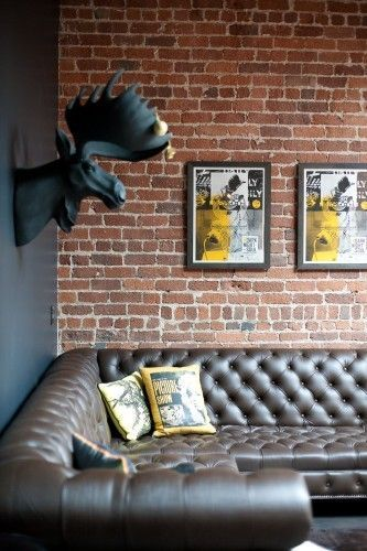 brown couch in front of brick with black moose head and yellow pillows and wall art