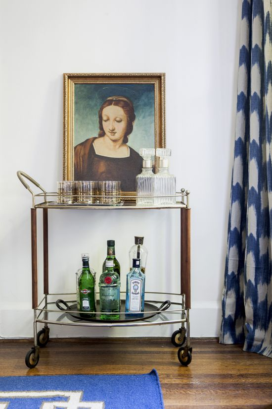 drinks trolley with bottles and glasses in front of painting