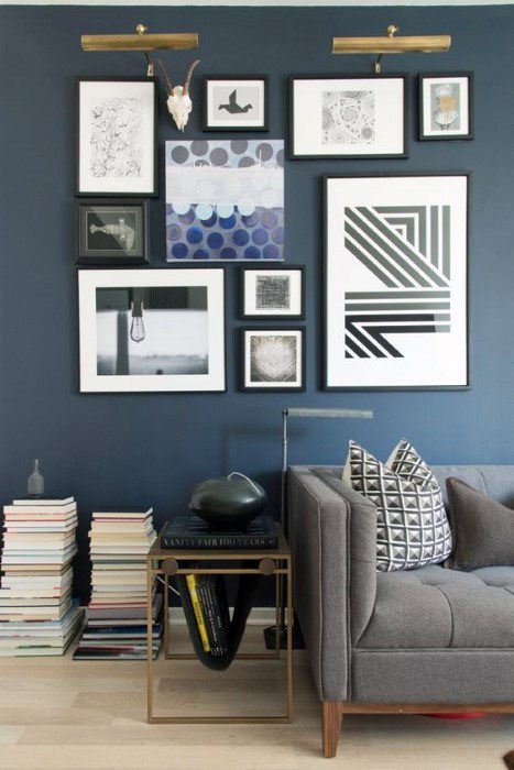 Grey couch with lighting and books in front of a blue wall