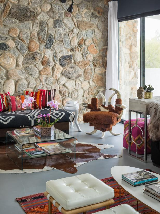 Bohemian living room wall decor with buffalo chair and stone wall with other bohemian decorating ideas