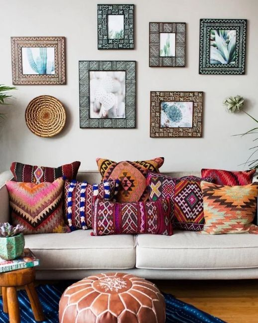Boho pillows on grey sofa with pictures on wall behind as bohemian decorating ideas
