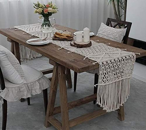 Macrame bohemian wooden dinner table with flowers and candles