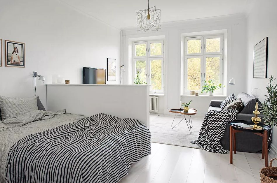 Split living room ideas as a bedhead work double time as a room divider in white bedroom with grey couch