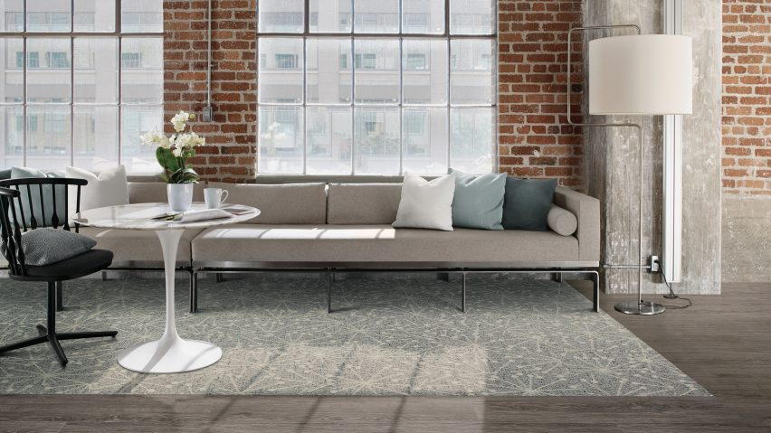 different zones with two types of flooring with grey couch in front of brick wall