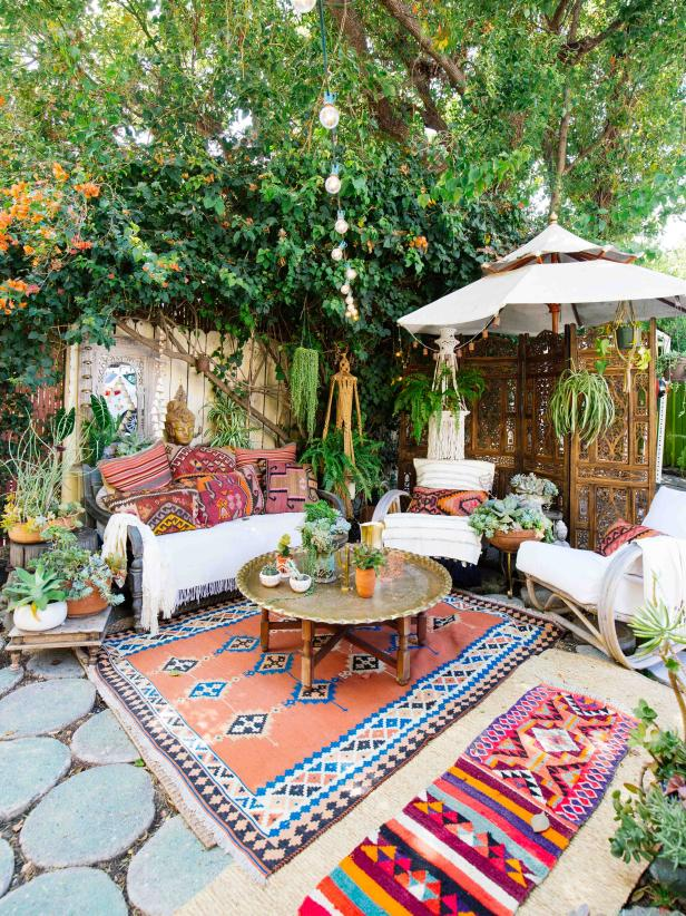 Bohemian decor in a sitting area with plants above lighting and umbrella