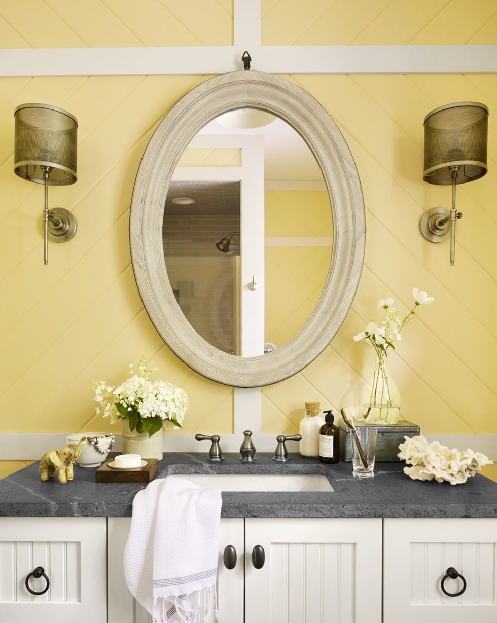 All Brass Sconces with rustic bathroom lighting ideas in yellow bathroom with round mirror and accessories
