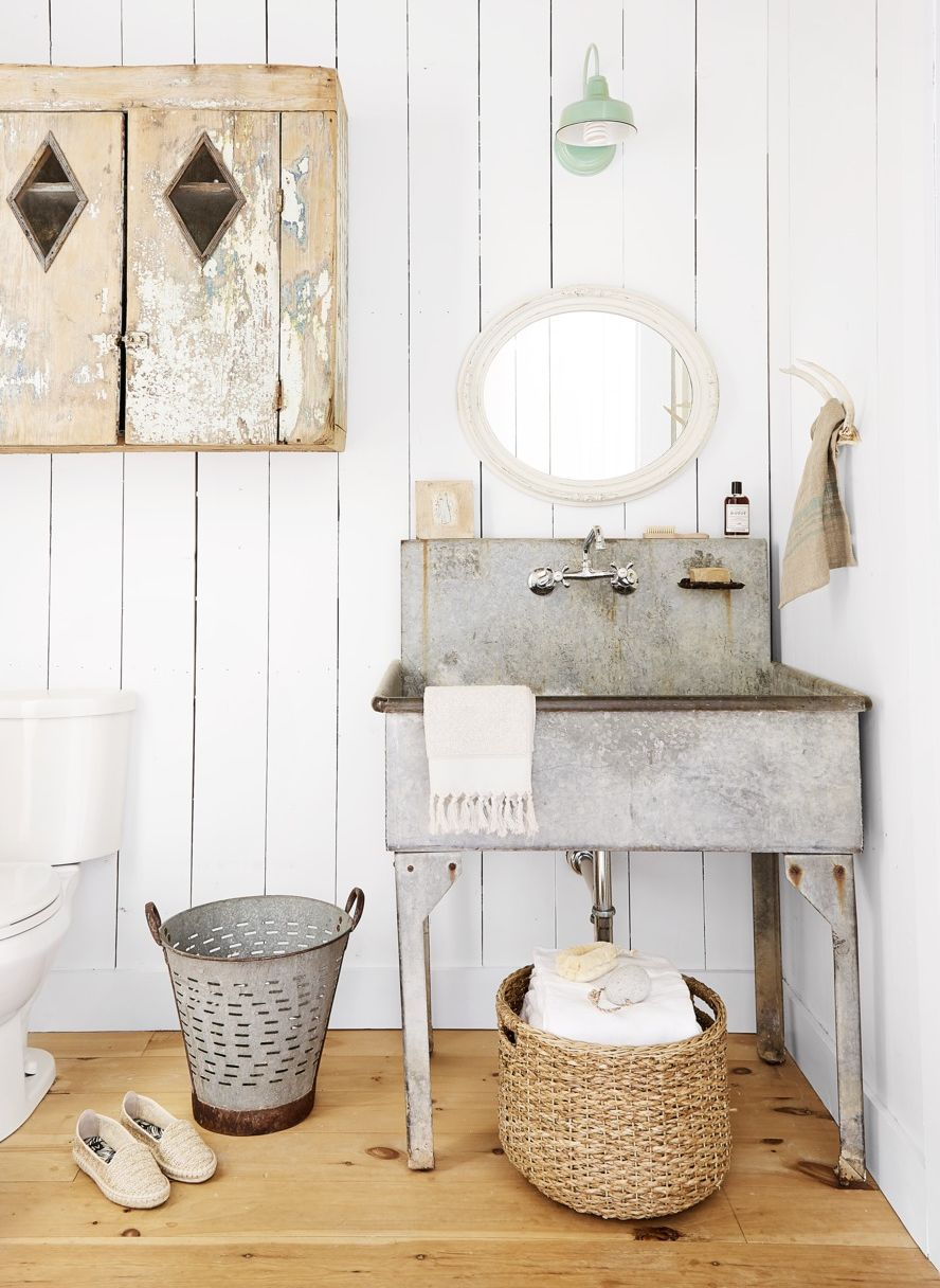 Barn Light Sconce in white bathroom with rustic metal sink and wood storage cabinet with basket
