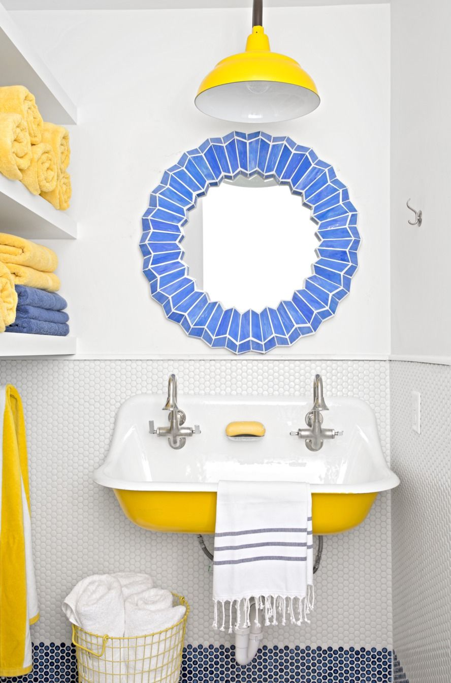 Barn Style Pendant Fixture in yellow in white bathroom with yellow sink bottom and basket with round mirror