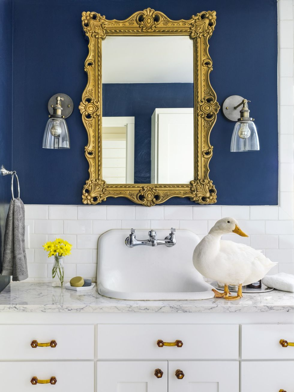 Bronze and Glass Sconces and rustic bathroom lighting ideas with white tile backsplash in dark blue with ornate square mirror and goose