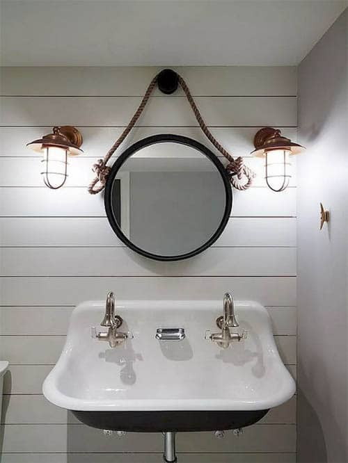 Copper Cage Style Sconces rustic bathroom lighting ideas with double sink and round mirror with black highlights