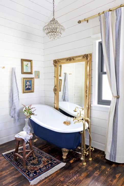 Crystal Chandelier in white bathroom with gold accents and large square mirror with artwork