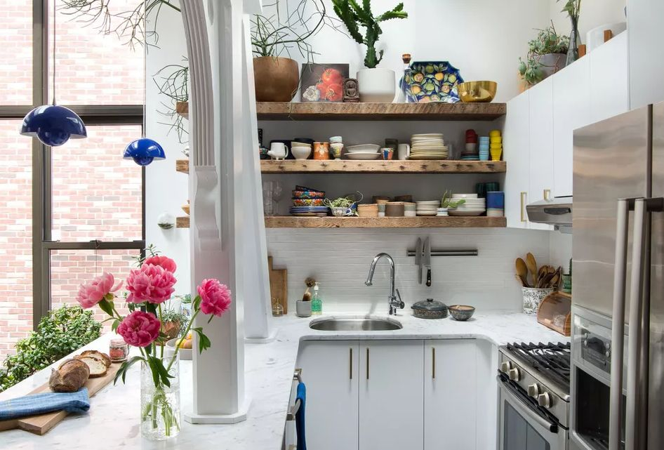 Small kitchen with wooden shelves with ceramics and flowers