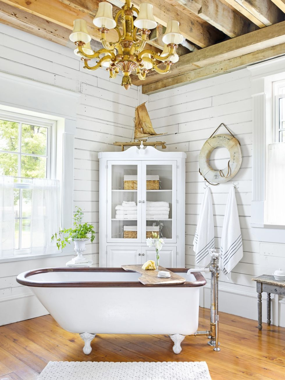 Eight Arm Chandelier in white bathroom with wooden floors and white storage cabinet and exposed beams