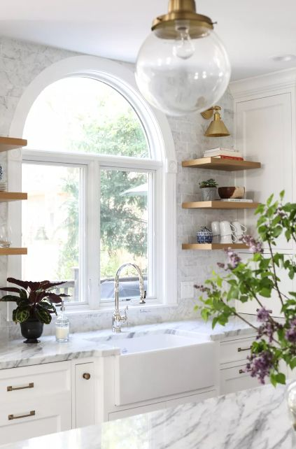 Kitchen with marble countertops and wooden open shelving with white cabinets
