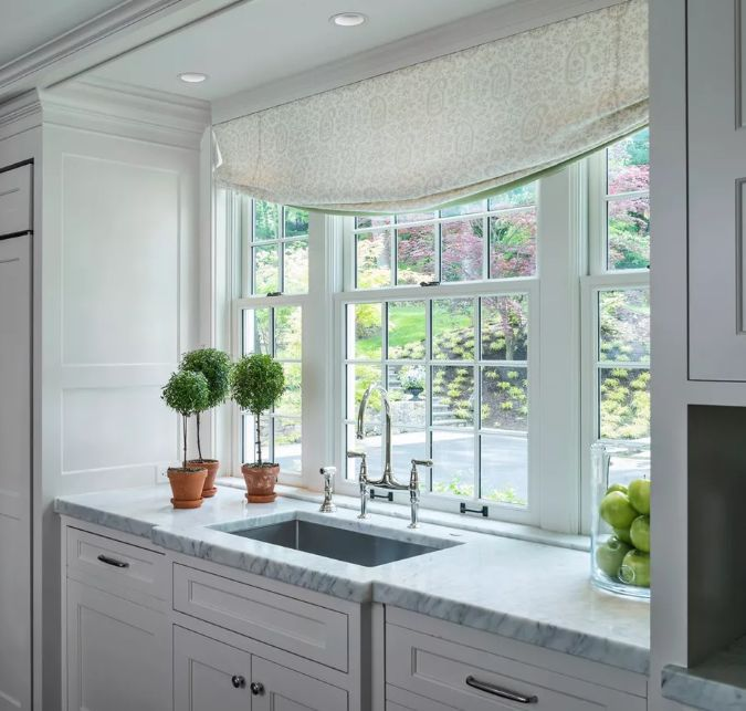 Kitchen decorating ideas for countertops in marble with three plants and large window