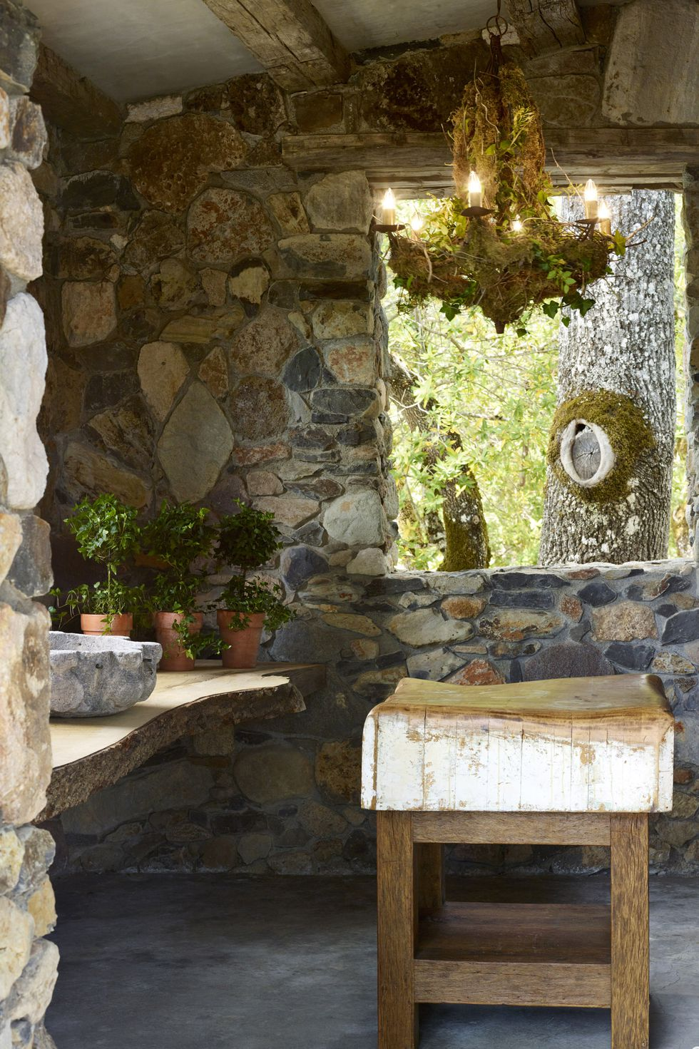 Stone kitchen with plants and chandelier and wood countertop