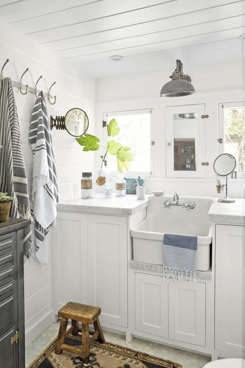 Industrial Barn Light in white bathroom with lower sink and mirrors and accessories