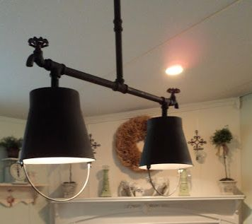 Iron buckets and old pipe pendant lamps in white bathroom with shelf and accessories