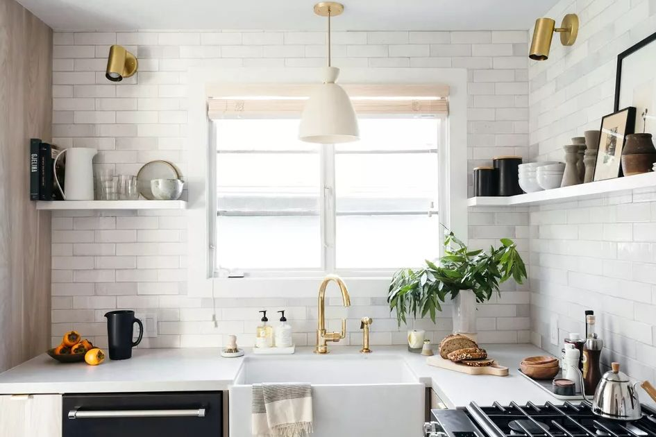 Kitchen decorating ideas for countertops with plants and storage shelves with gold lighting