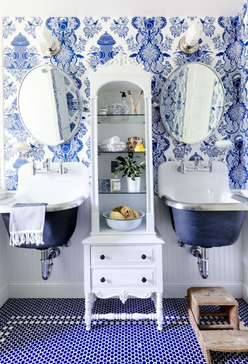Milk Glass Sconces with tall storage cabinet with blue wallpaper and blue tile and two sinks