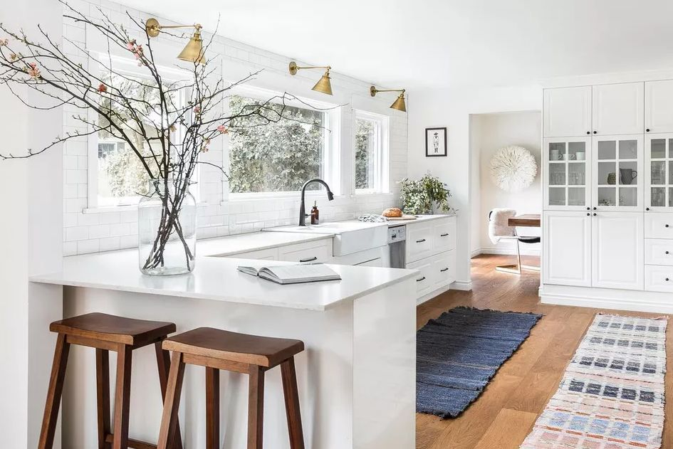 White kitchen with large windows and above lighting with plants