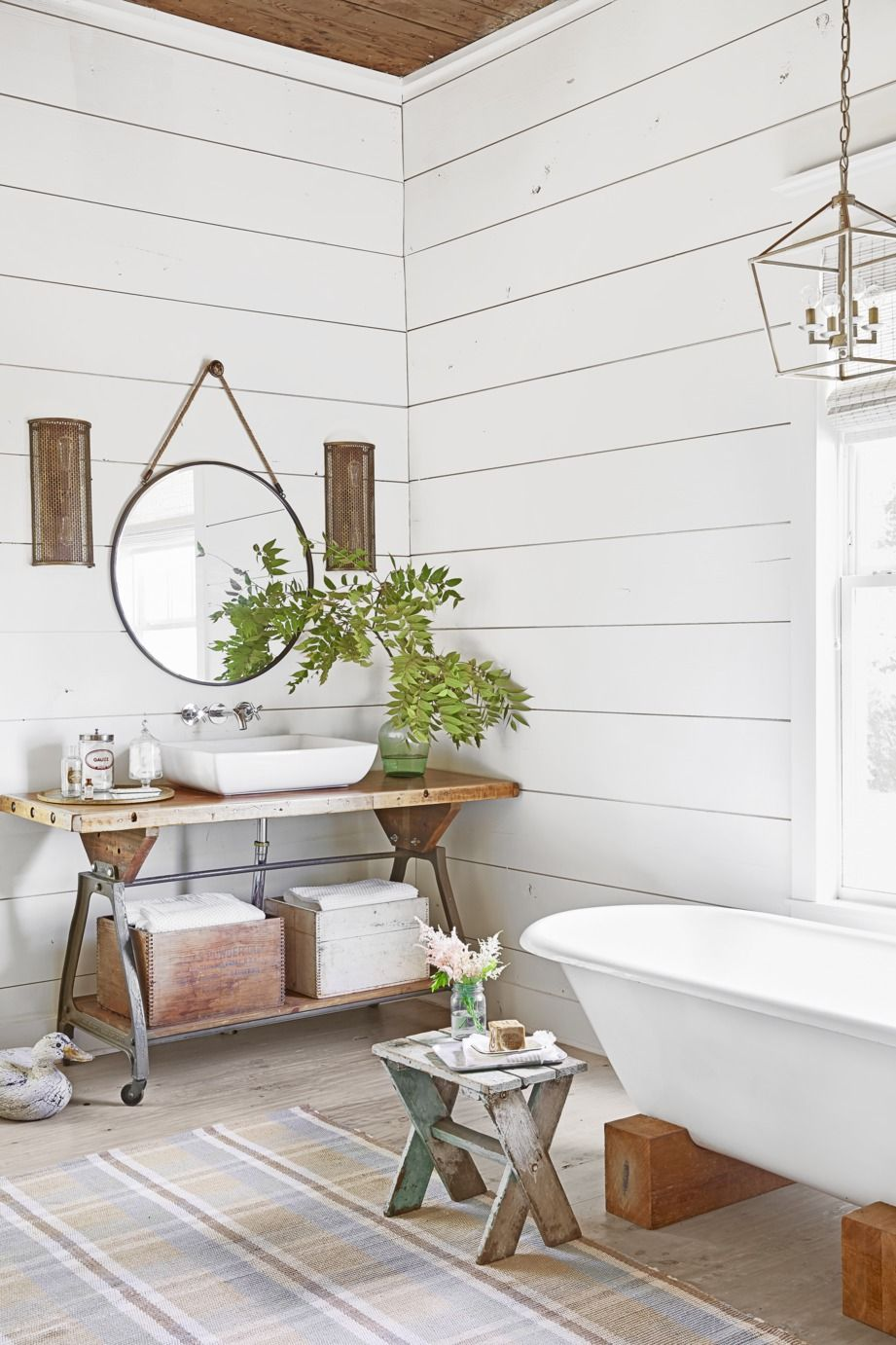 Open Lantern and Bronze Mesh Sconces in white bathroom with plants and accessories and round hanging mirror